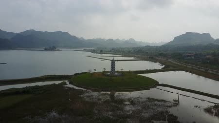 ninh : Pagoda in the middle of wetlands in Vietnam. Mountain silhouettes in the background and a cloudy sky above. Aerial shot. Pull back shot. Stock Footage