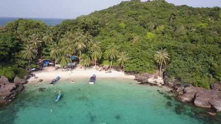 poblíž : Boats, yacht and people near the coast of an island in the Gulf of Thailand. Beach sands and lush vegetation in the background. Aerial shot.