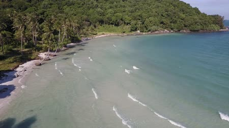 bitkiler : Sea waves with tropical island forest in the background. Drone shot. Wide shot.