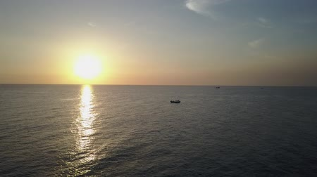 uklidňující : Sunset and horizon over the Gulf of Thailand. Silhouettes of boats sailing in the distance. Aerial shot. Panorama.