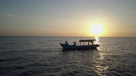 soothing : Sunset and horizon over the Gulf of Thailand. Silhouettes of a boatmen sailing. Aerial shot. Panorama.