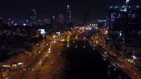 urban birds : Night view aerial of Ho Chi Minh City. Street traffic and high rise buildings filmed from a drone descending down to the Saigon river. Establishing shot. Drone shot. Stock Footage
