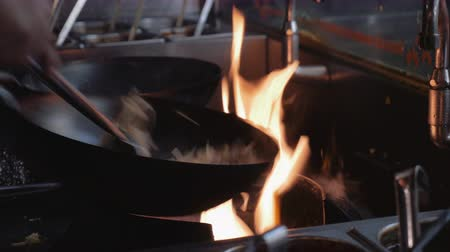 gotowanie : Stirring noodles in a wok. Commercial kitchen chefs stirring noodles in woks with stove flames burning. Close up. Wideo