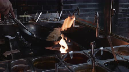 wok food : Wok cooking in commercial kitchen. Tossing and stirring noodles. Rack focus. Stock Footage