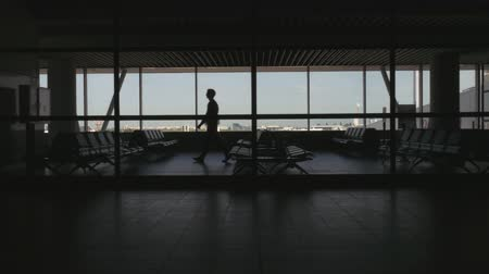 comprimento total : Silhouette of man walking across an airport waiting area. Long shot. Profile. Stock Footage