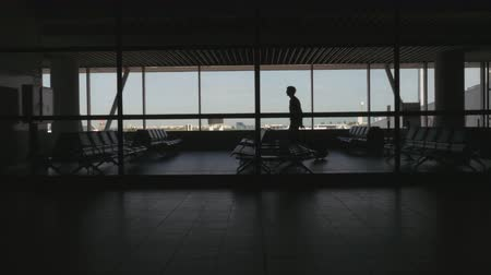 lugares sentados : Silhouette of passenger waiting in an airport seating area, standing and looking out the window. Long shot. Rear View.