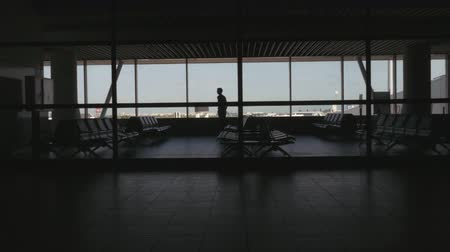 comprimento total : Airport passenger taking pictures of the sky while waiting in a seating area. Long shot. Rear View. Stock Footage