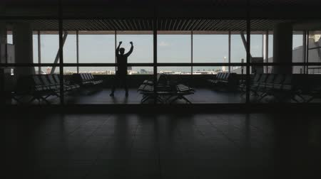 comprimento total : Silhouette of man dancing in an airport waiting area. Long shot. Stock Footage