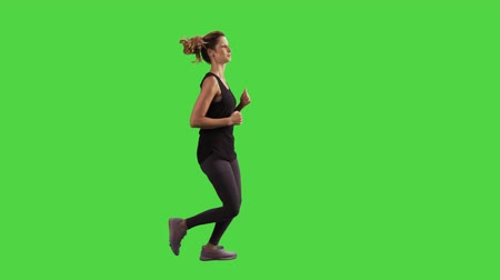 trabalhar fora : A young woman running in a full body sideways shot over a green screen, slows down and stops. Vídeos