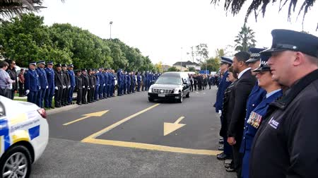 elesett : Shot of a funeral with police, dogs, motocycles & helicopter as guard of honor