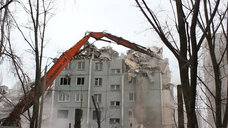 deconstruction : VOLGOGRAD, RUSSIA - FEBRUARY 02, 2016: Urban scene. Demolition apartment building using excavator with hydraulic mechanical arm jaws for new construction. Stock Footage