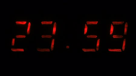 fósforo : Digital clock with fluorescent display shows the time of 23 hours 59 minutes to 00 hours 00 minutes in the red on a black background