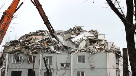 buldozer : VOLGOGRAD, RUSSIA - FEBRUARY 02, 2016: Urban scene. Demolition apartment building using excavator with hydraulic mechanical arm jaws for new construction. Dostupné videozáznamy