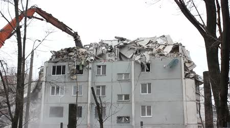 yıkım : Urban scene. Demolition apartment building using excavator with hydraulic mechanical arm jaws for new construction. Stok Video