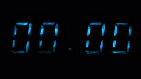 fósforo : Digital clock with fluorescent display shows the time of 00 hours 00 minutes to 00 hours 01 minutes in the blue on a black background
