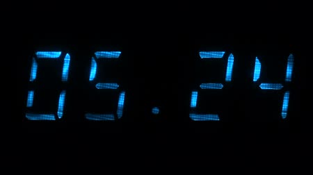 fósforo : Rapid adjustment of time on the digital clock display, blue digits on a black background.