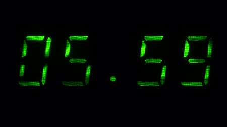 fósforo : Digital clock with fluorescent display shows the time of 05 hours 59 minutes to 06 hours 00 minutes in the green on a black background