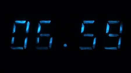 fósforo : Digital clock with fluorescent display shows the time of 06 hours 59 minutes to 07 hours 00 minutes in the blue on a black background