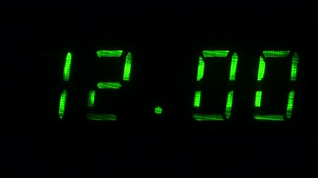 fósforo : Digital clock with fluorescent display shows the time of 11 hours 59 minutes to 12 hours 00 minutes in the green on a black background