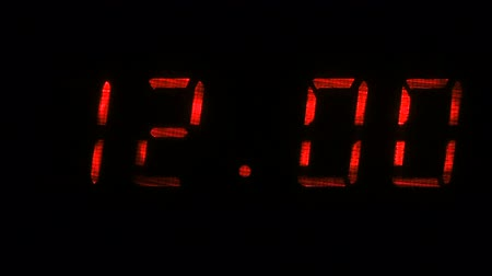 fósforo : Digital clock with fluorescent display shows the time of 11 hours 59 minutes to 12 hours 00 minutes in the red on a black background