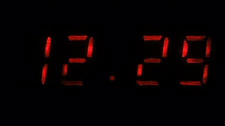 fósforo : Digital clock with fluorescent display shows the time of 12 hours 29 minutes to 12 hours 30 minutes in the red on a black background
