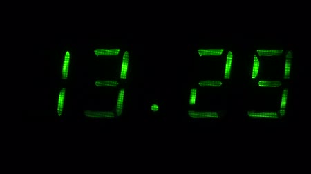 fósforo : Digital clock with fluorescent display shows the time of 13 hours 29 minutes to 13 hours 30 minutes in the green on a black background