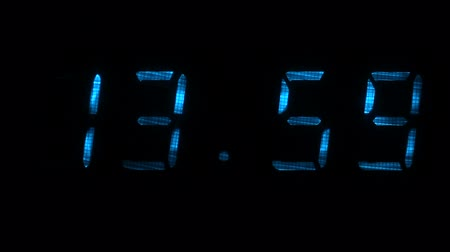 fósforo : Digital clock with fluorescent display shows the time of 13 hours 59 minutes to 14 hours 00 minutes in the blue on a black background