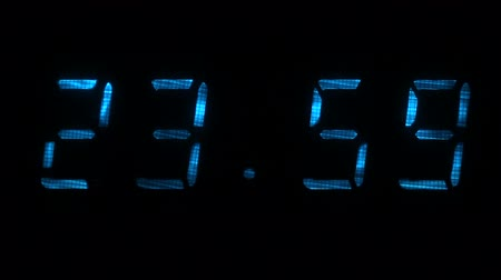 fósforo : Digital clock with fluorescent display shows the time of 23 hours 59 minutes to 00 hours 00 minutes in the blue on a black background