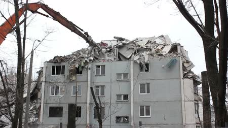 deconstruction : Urban scene. Demolition apartment building using excavator with hydraulic mechanical arm jaws for new construction. Stock Footage
