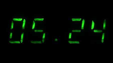 fósforo : Rapid adjustment of time on the digital clock display, green digits on a black background.