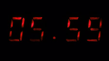 fósforo : Digital clock with fluorescent display shows the time of 05 hours 59 minutes to 06 hours 00 minutes in the red on a black background Vídeos