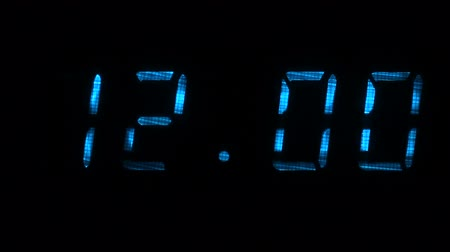 fósforo : Digital clock with fluorescent display shows the time of 11 hours 59 minutes to 12 hours 00 minutes in the blue on a black background