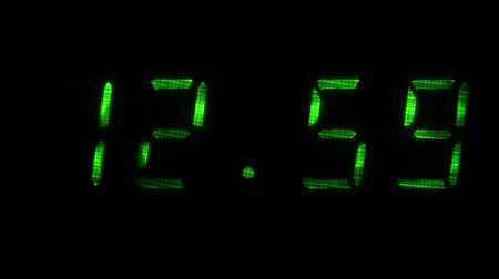 fósforo : Digital clock with fluorescent display shows the time of 12 hours 59 minutes to 13 hours 00 minutes in the green on a black background