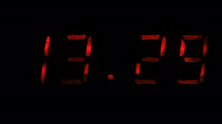fósforo : Digital clock with fluorescent display shows the time of 13 hours 29 minutes to 13 hours 30 minutes in the red on a black background
