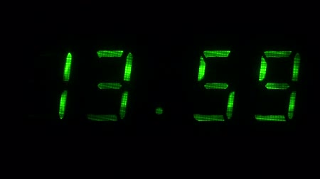 fósforo : Digital clock with fluorescent display shows the time of 13 hours 59 minutes to 14 hours 00 minutes in the green on a black background Vídeos