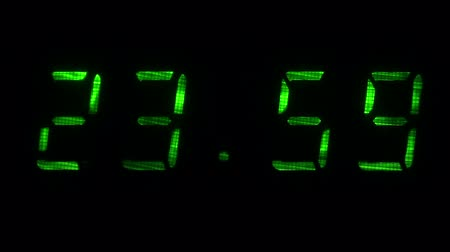 fósforo : Digital clock with fluorescent display shows the time of 23 hours 59 minutes to 00 hours 00 minutes in the green on a black background Vídeos
