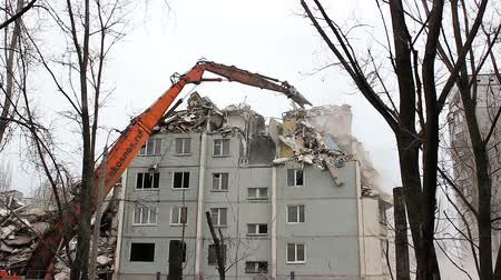 yıkım : VOLGOGRAD, RUSSIA - FEBRUARY 02, 2016: Urban scene. Demolition apartment building using excavator with hydraulic mechanical arm jaws for new construction. Stok Video