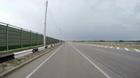 zadní : The car goes from an exit on high speed highway on an empty line. Rear view. The storm clouds in the sky.