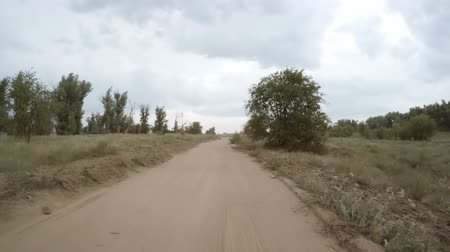 driveway : A view of the rural dirt road from camera installed on back of the car driving along this country road. Riding on a rough roadway. Traces of tires on the sand.