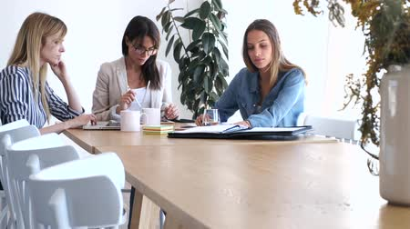área de trabalho : Video of pretty young businesswomen working on new ideas in co-working space.