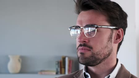distraído : Video of handsome young business man looking sideways in the office.