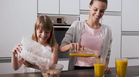 Video of pretty young mother and her daughter preparing breakfast in the kitchen at home.