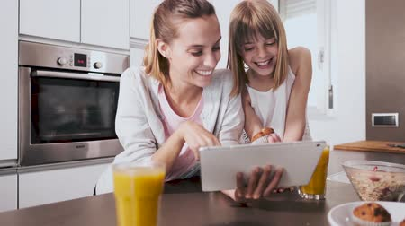 Video of pretty young mother and daughter using digital tablet while having breakfast in the kitchen at home.