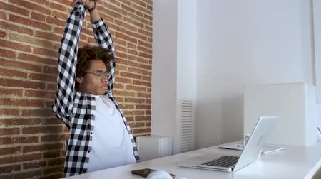 Video of tired young african american man with eyeglasses stretching while working with laptop at home. Vídeos