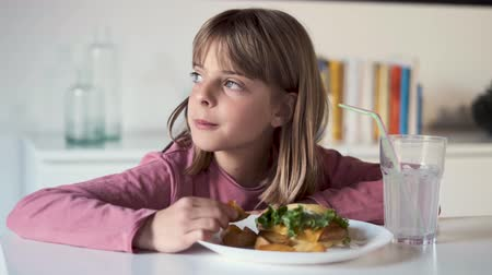 чизбургер : Video of bored little girl looking sideways while eating a full hamburger with potatoes at home.