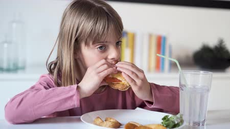 Video of pretty little girl eating a complete hamburger at home. Dostupné videozáznamy