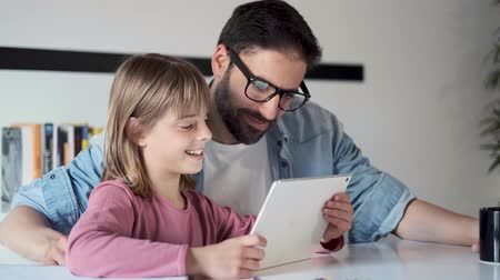 Video of handsome young father with his daughter using they digital tablet at home. Vídeos