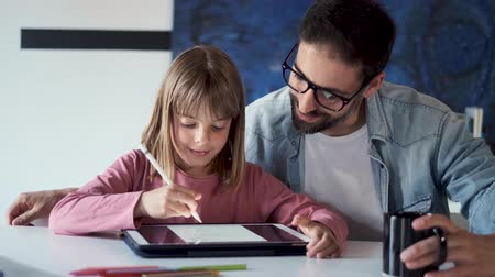 Video of handsome young father with his daughter drawing with digital tablet at home.