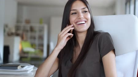 Video of smiling young business woman talking on mobile phone while sitting in the office. Vídeos