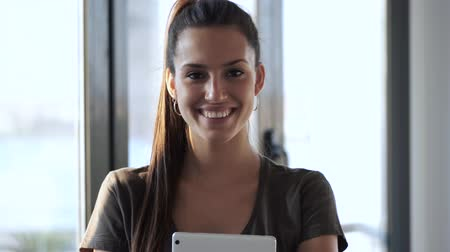 Video of smiling young business woman looking at camera while standing in the office.